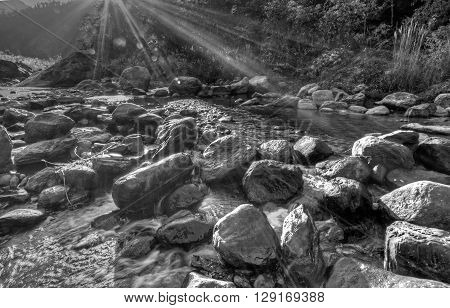 River water flowing through rocks at dawn sun light beams on the water beautiful Reshi River Sikkim India - black and white stock image of rivers in India