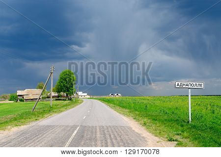 Country road with a signpost on the background of dark stormy sky before the rain