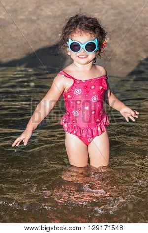 Smiling baby girl in sunglasses on the beach