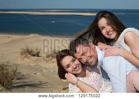Smiling Family Piggybacking Their Daughter At The Beach