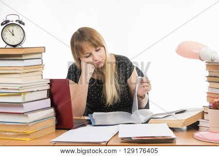 Student Sadly Looking At Turning The Pages In A Folder At The Desk Among The Stacks Of Books