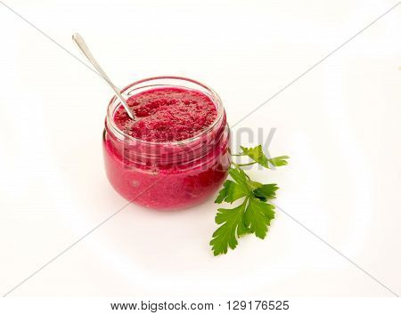 Delicious Beet Horseradish in Glass Gravy Boat isolated on Wooden background