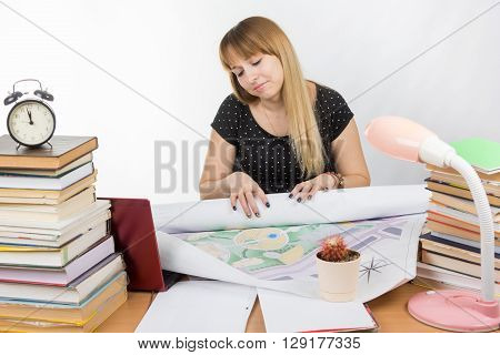 Girl Design Student Sitting At A Desk And Is Tired Deploys A Large Drawing