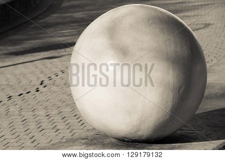 architectural abstract element in the form of the sphere closeup on an indistinct background of a sidewalk stone blocks of beige color