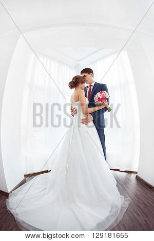 Wedding couple in love. Beautiful bride in white dress with brides bouquet and handsome groom in blue suit standing and embracing each other indoors at home, white bright room with big window High key, made on fisheye lens photo.