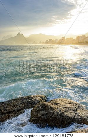 Sunset on Ipanema beach in Rio de Janeiro with the Leblon beach and Two Brothers hill and Gavea stone in background