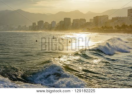 Sunset on Ipanema beach in Rio de Janeiro with the Leblon beach and Rio de Janeiro hills in the background
