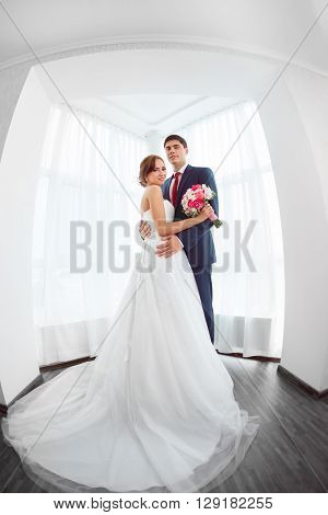 Wedding couple in love. Beautiful bride in white dress with brides bouquet and handsome groom in blue suit standing and embracing each other and lookin at camera indoors at home, white bright room with big window High key, made on fisheye lens photo.