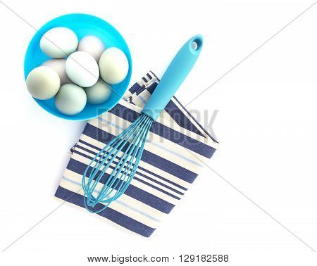 Eggs in a blue bowl with a wisk on a white background shot from above