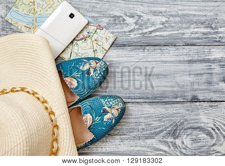 Vacation and travel items. Travel concept - telephone shoes map hat on a wooden background