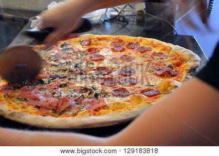 Human hands cutting italian pizza on a pizzeria