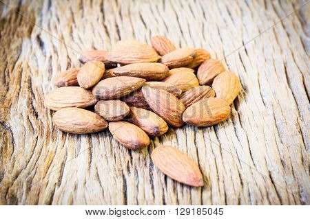 almonds on old wooden table background .