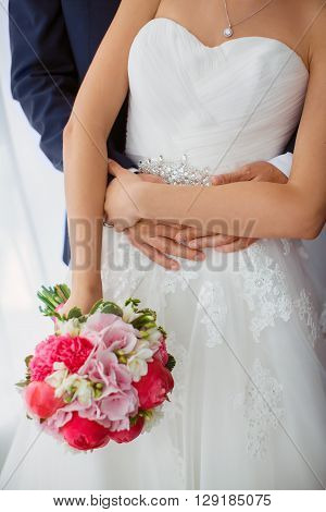 Wedding couple details indoors. Beautiful bride in white dress and pink bridal bouquet of flowers and groom in blue suit close-up. No face, only body and hands.