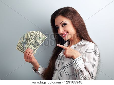 Happy successful young pretty woman showing the finger on dollars in hand with toothy smiling on blue background