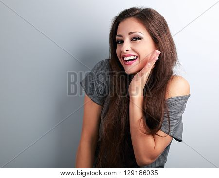 Happy Toothy Laughing Brunette Young Woman With Hand Near Face On Blue Background