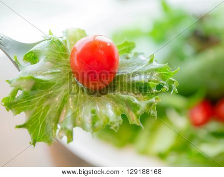Tomato with vegetable on silver spoon over salad plate selective focus