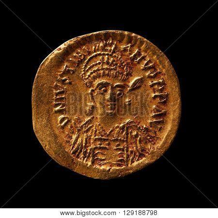Ancient golden byzantine coin of emperor Justinianus closeup macro shot