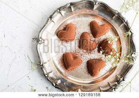 Handmade candies Tiramisu in eart shape on metal plate. Valentine's Day and Mother's Day concept with copy space. Top view.