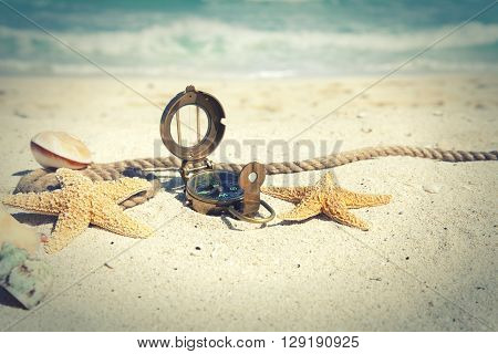 Cross-processed selective focus compass with shells and rope on an ocean beach