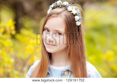 Smiling teen girl 12-14 year old wearing floral hairband outdoors. Looking at camera.