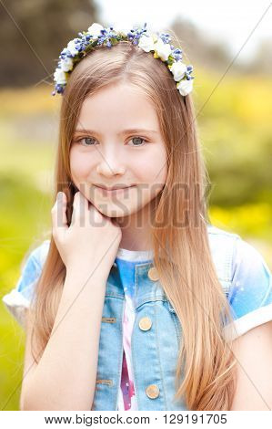 Smiling teenage girl 12-14 year old wearing floral hairband outdoors. Looking at camera. Childhood.