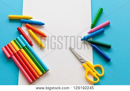 The concept of the artistic activity of the child. Colorful school supplies. Album for drawing and colored pencils on a blue background.