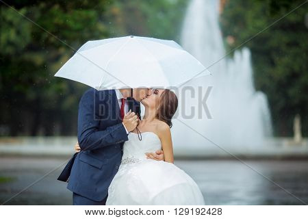 Happy wedding couple in a rainy wedding day walking outdoors in park with white umbrella in rainy weather. Bride and groom are kissing and embracing.