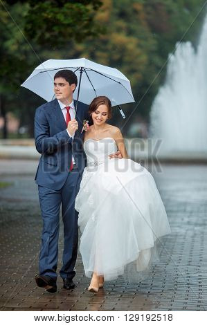 Happy wedding couple in a rainy wedding day outdoors in park with white umbrella in rainy weather. Bride and groom are embracing and walking in park.