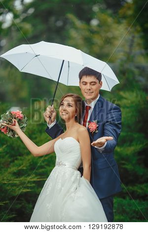 Happy wedding couple in a rainy wedding day walking outdoors in park with white umbrella in rainy weather. Bride and groom are having fun with the rain.
