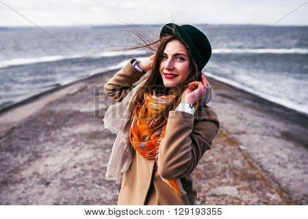 Emotive Portrait Of A Fashionable Model In White Coat And Hat Posing At The Winter Seaside.   French