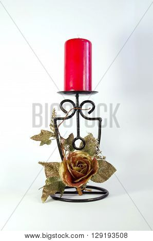 red candle in a metallic candlestick decorated a decorative rose
