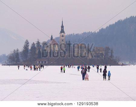 LAKE BLED, SLOVENIA - FEBRUARY 12 2012: Families enjoying a frozen Lake Bled.