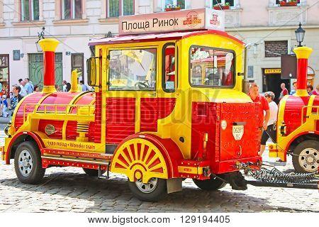 LVIV, UKRAINE - JUNE 29, 2014: Sightseeing car train in the center of Lviv Market square, Ukraine