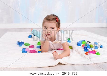 Pretty child girl playing with toys constructor
