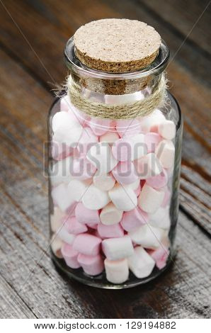 Pink and white marshmallows spilling from a storage jar over old wood background. Vintage effect with intentional vignette