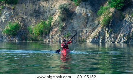 Man Kayaking On The River And Drone Near