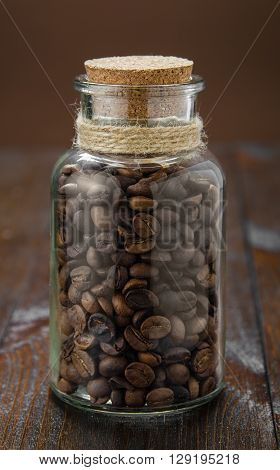 Coffee in a vintage jar on wooden table, closeup
