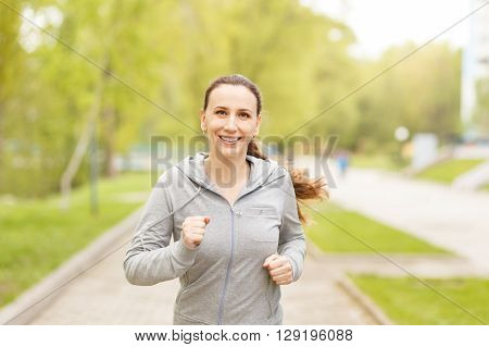 Young smiling woman jogging in park in the morning. Beautiful caucasian girl running outdoors