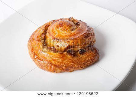 Freshly baked sweet roll on a white plate