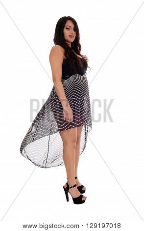 A lovely East Indian woman standing in a lovely dress in high heels looking down isolated for white background.