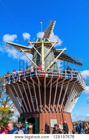 Lisse Netherlands - April 23 2016: windmill at Keukenhof with unidentified people. Its one of the worlds largest flower gardens. Approximately 7 million flower bulbs are planted annually in the park