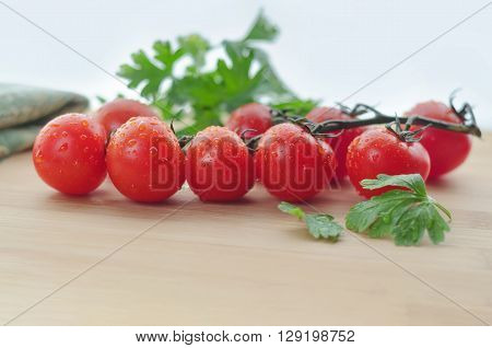 Tomatoes on a branch and parsley, are on the table, the natural light and bokeh.