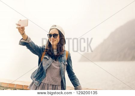 Beautiful Asian traveler taking selfie with ocean view background soft warm light tone ** Note: Soft Focus at 100%, best at smaller sizes
