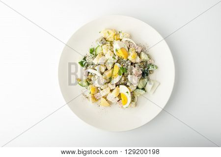 Olivier salad in ceramic plate on white background horizontal