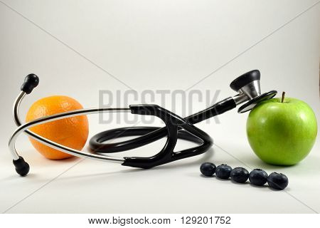 Health and wellness concept. A doctor's stethoscope placed next to an apple, orange and blueberries.