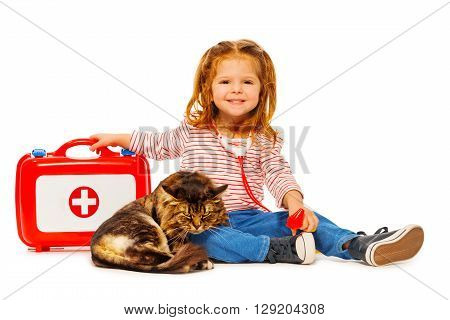 Little girl playing veterinarian with medicine box treating cat, isolated on white