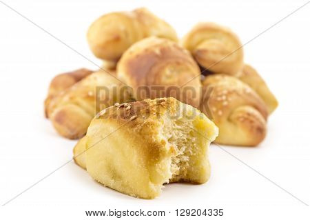 Fresh Serbian pastry rolls with cheese and sesame, kifla kiflice, one bitten, isolated on white background