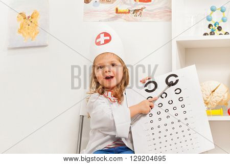 Cute little girl playing doctor with oculist's sign and pointer at office.