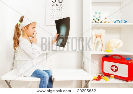 Cute young girl doctor in whites and cap holding a skull x-ray in the medical room.