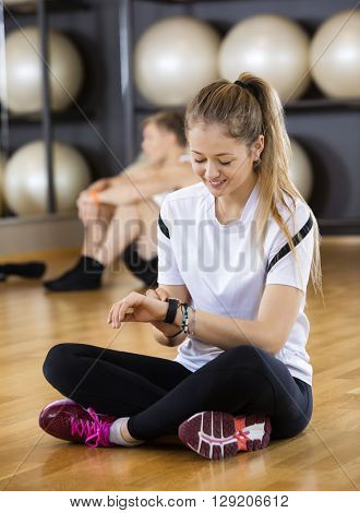 Woman Using Activity Tracker While Sitting In Gym